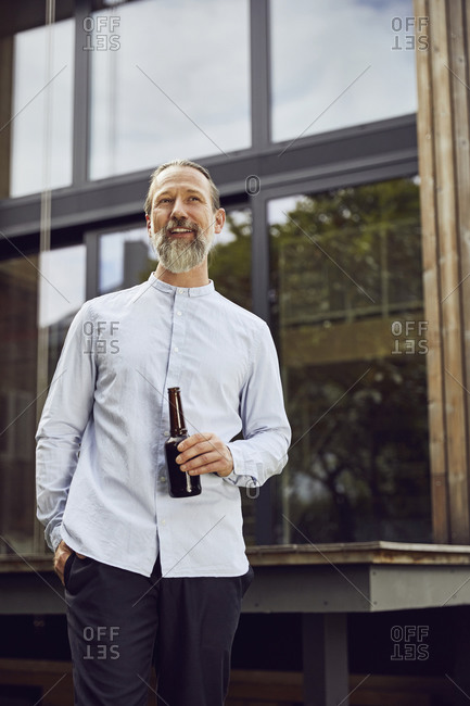 Bearded mature man holding beer bottle while standing against tiny house