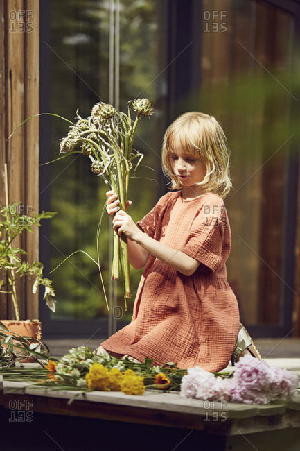 Girl arranging flowers while kneeling outside house at porch