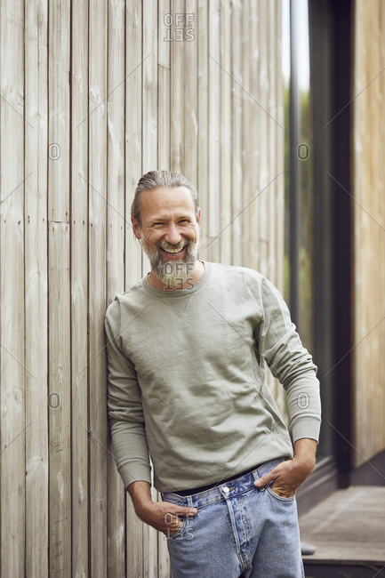 Happy bearded mature man with hands in pockets standing by wall at yard