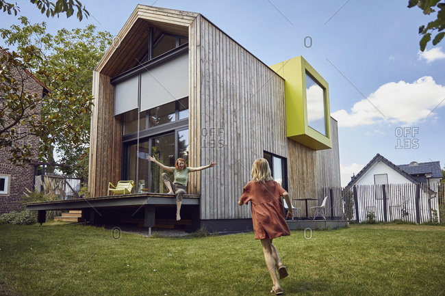 Girl running towards happy mother sitting outside tiny house