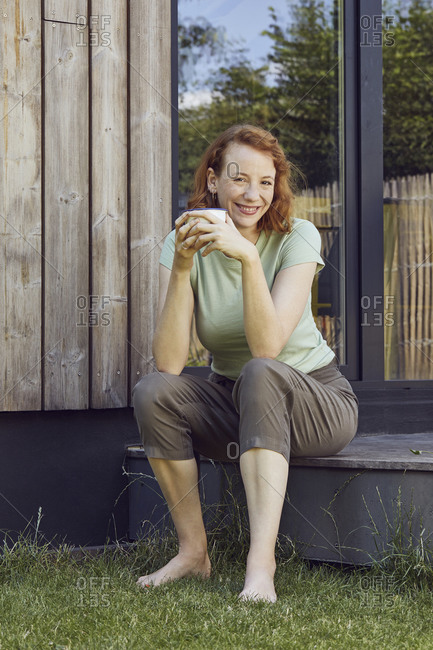 Smiling mid adult woman holding coffee cup while sitting outside tiny house
