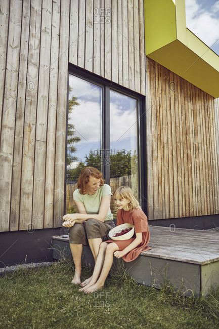 Mother and daughter with cherries sitting outside tiny house
