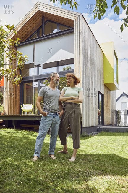Mature man with hands in pockets looking at woman while standing outside tiny house