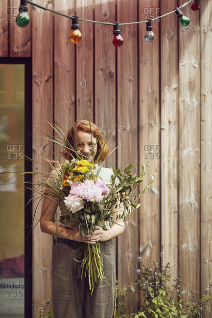 Smiling mid adult woman holding flowers while standing against tiny house