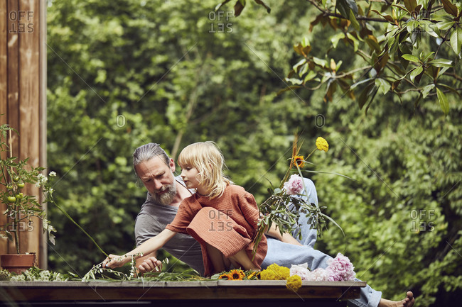 Mature man lying by daughter arranging flowers in yard