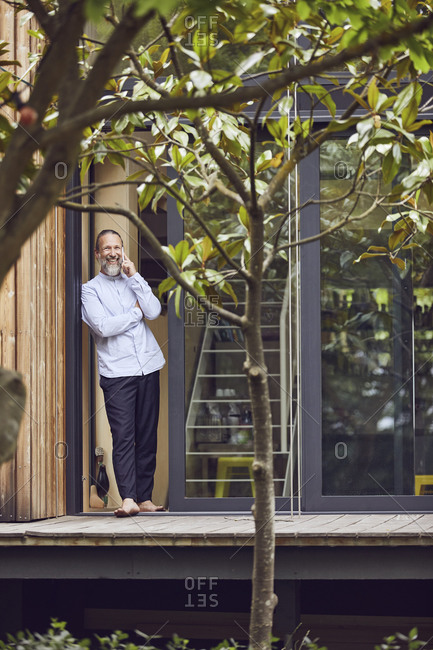 Bearded man talking over smart phone while standing at entrance of in tiny house