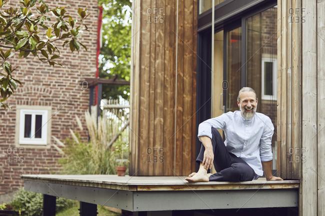 Happy bearded man sitting on hardwood floor outside tiny house