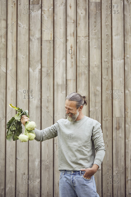 Smiling mature man holding cabbages while standing against house