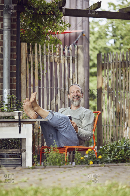 Smiling bearded mature man sitting on chair outside tiny house
