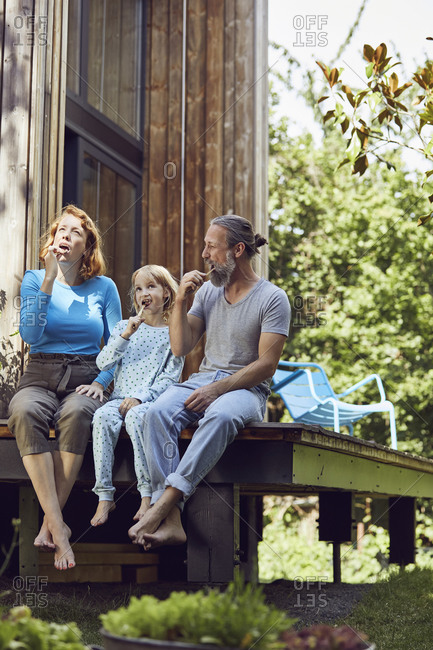Daughter with parents brushing teeth while sitting outside tiny house