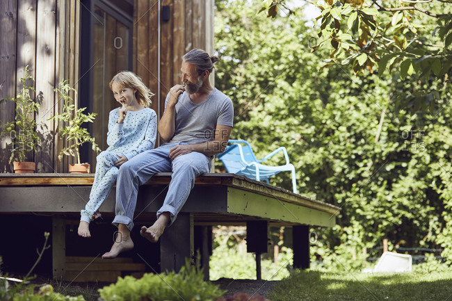 Father and daughter brushing teeth while sitting outside tiny house