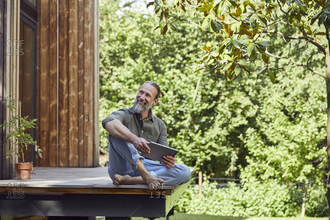 Smiling man with digital tablet looking away while sitting outside tiny house