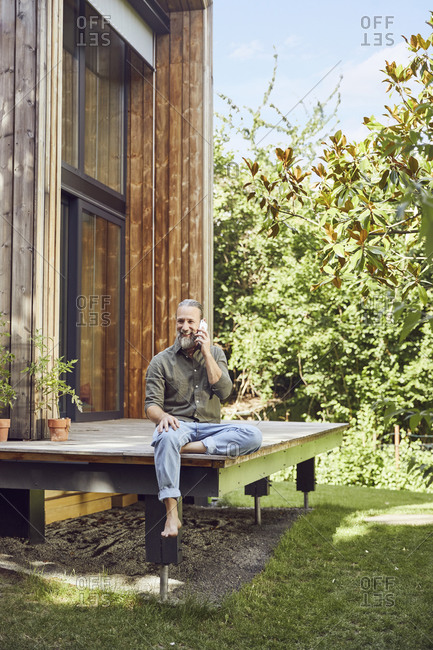 Bearded mature man talking over mobile phone while sitting outside tiny house