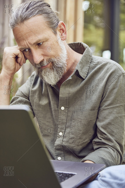 Close-up of thoughtful bearded mature man using laptop while sitting in yard