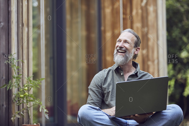 Cheerful mature man with laptop looking away while sitting outside tiny house