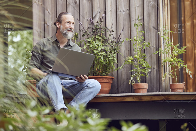 Thoughtful bearded man with laptop sitting outside tiny house