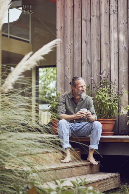 Thoughtful mature man holding coffee cup while sitting outside tiny house