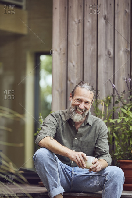 Cheerful mature man holding coffee cup while sitting outside tiny house