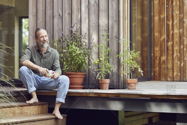 Smiling bearded man holding coffee cup while sitting outside tiny house