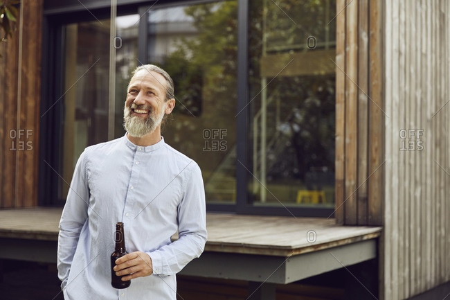 Smiling mature man holding beer bottle while standing against tiny house