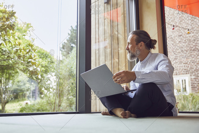 Bearded mature man with laptop looking through window while sitting in tiny house
