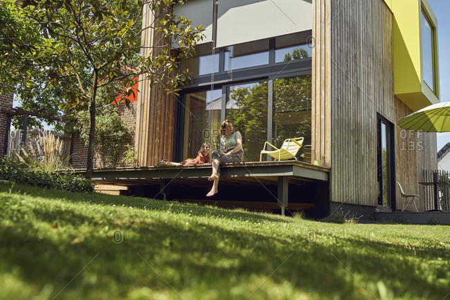 Mother and daughter relaxing outside tiny house in yard
