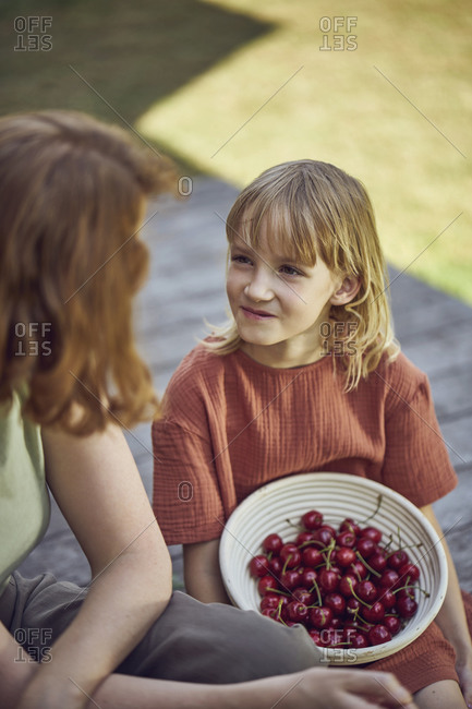 Mother sitting with eating cherries while sitting in yard
