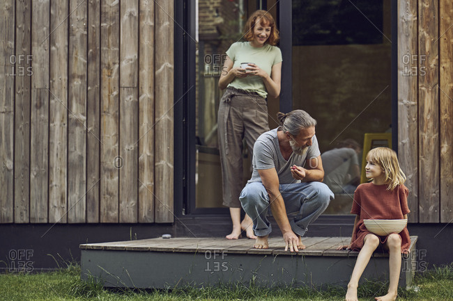 Woman looking at father and daughter eating cherries outside tiny house