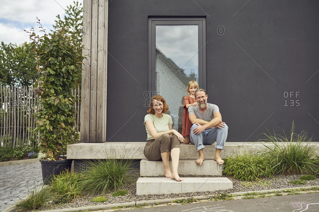 Smiling parents with girl sitting on steps outside tiny house