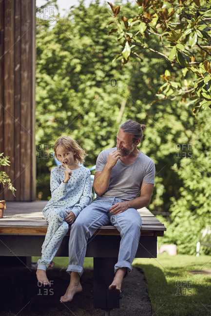 Father and daughter brushing teeth while sitting outside house in yard