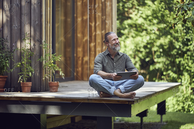 Bearded mature man holding digital tablet contemplating while sitting outside tiny house
