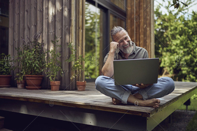 Smiling mature man using laptop while sitting against tiny house