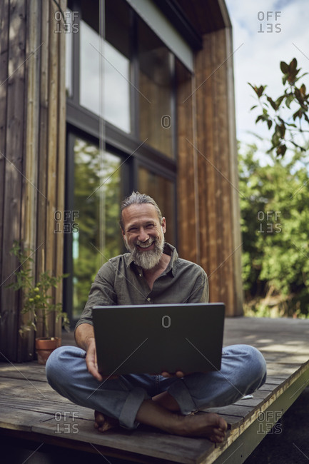 Smiling mature man with laptop sitting against tiny house