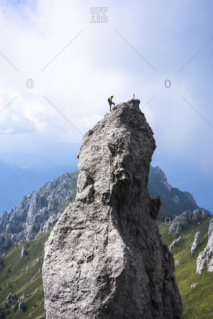 Male hiker standing on top of mountain against sky- European Alps- Lecco- Italy
