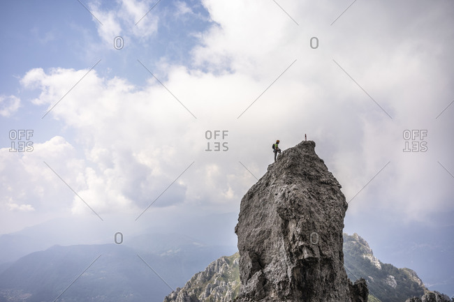 Male hiker standing on top of mountain against cloudy sky- European Alps- Lecco- Italy