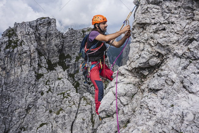 Male mountaineer with rope climbing on mountain- European Alps- Lecco- Italy