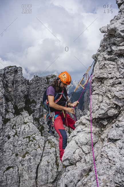 Male mountaineer with rope balancing on mountain- European Alps- Lecco- Italy