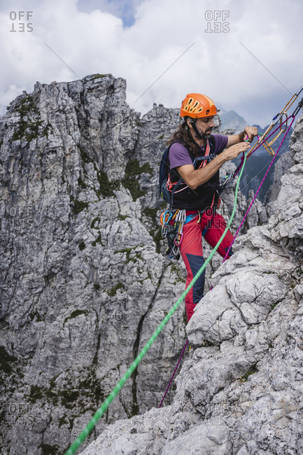 Mature man with ropes standing on mountain- European Alps- Lecco- Italy