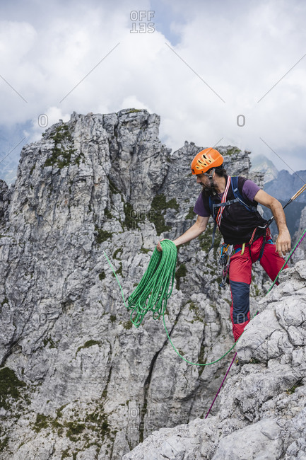 Mature man holding ropes while standing on European Alps- Lecco- Italy