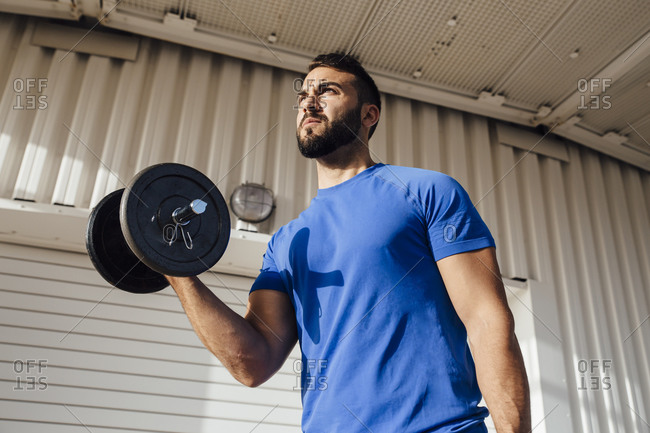 Sportsman lifting dumbbell while standing against wall