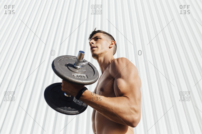 Young athlete lifting dumbbell while standing against wall