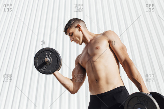 Shirtless athlete lifting dumbbell while standing against wall