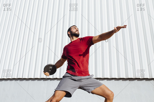 Young man practicing disc throw while standing against wall