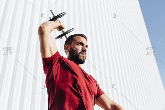 Young bearded man lifting dumbbell up while standing against wall