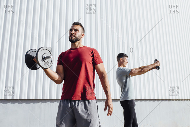 Young athletes exercising with sports equipment while standing against wall