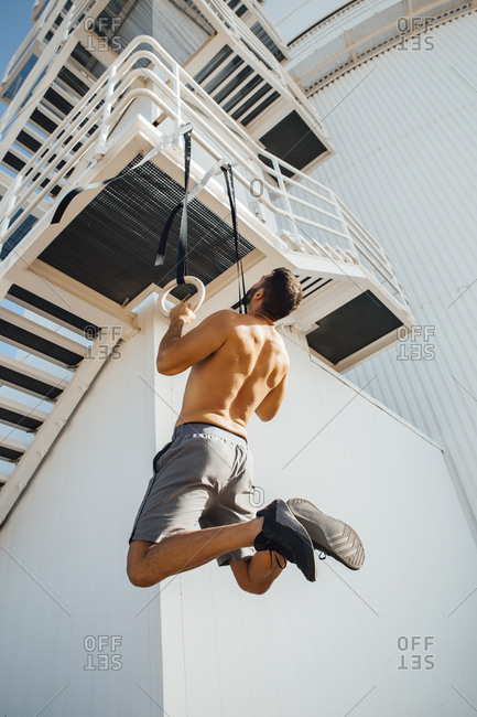 Sportsperson exercising while hanging on ring at staircase outdoors