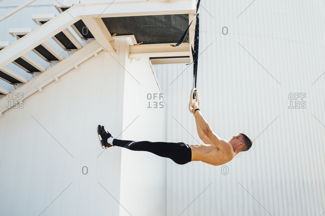 Athlete balancing body weight while hanging on ring at staircase outdoors