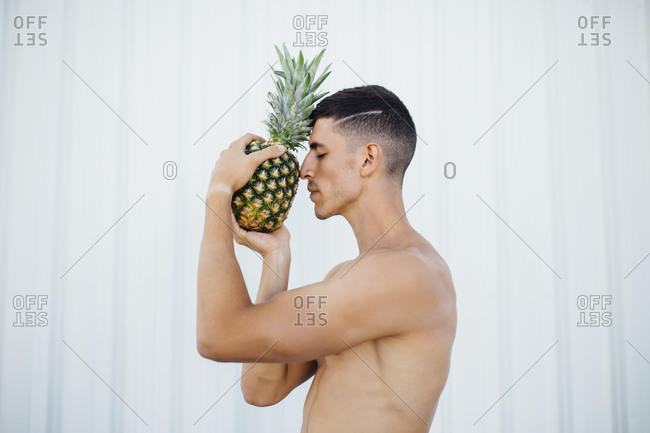 Young man smelling pineapple while standing against wall
