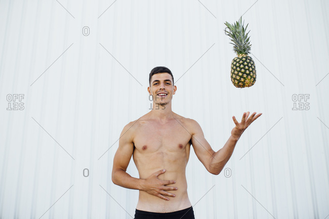 Smiling man playing with pineapple while standing against wall