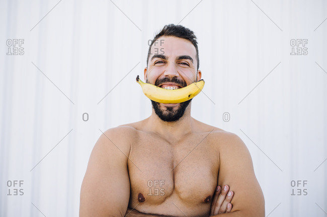 Young man holding banana in mouth while standing against wall